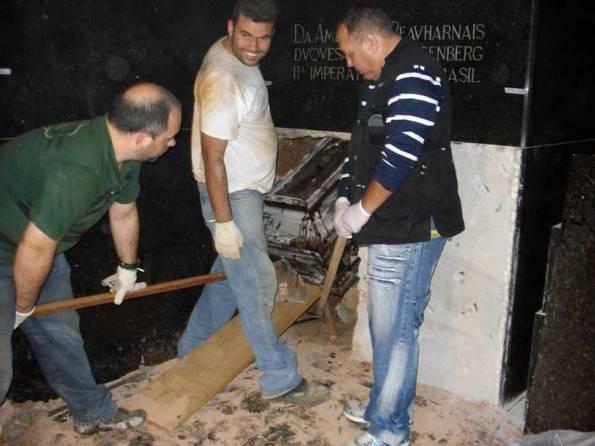 Figura 1 Eu escorando o caixão, Célio próximo do caixão e Valter Muniz escorando a rampa por onde o caixão vinha deslizando.